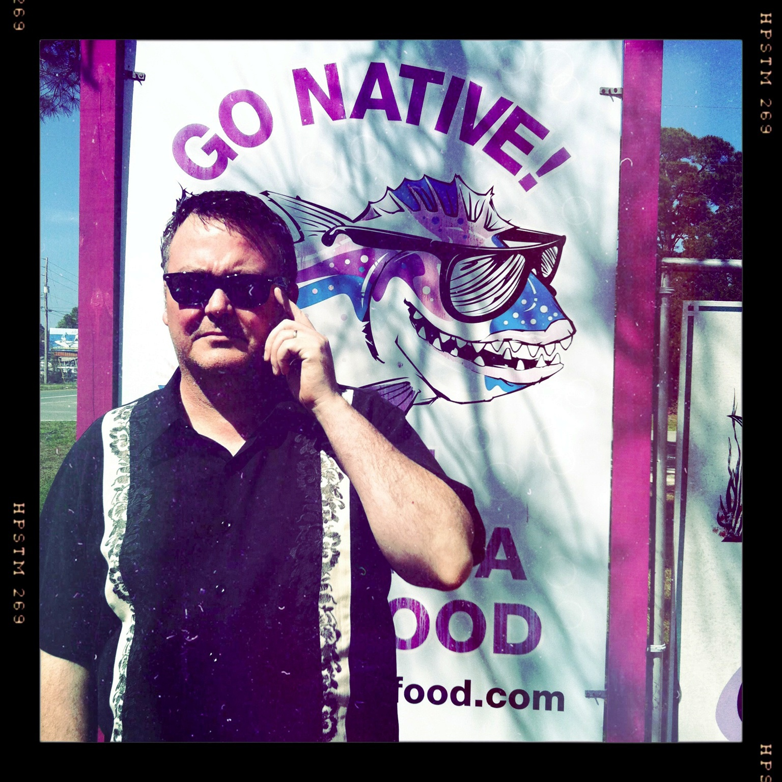 Art Coulson adjusts his eyeglasses in front of a sign that reads Go Native!