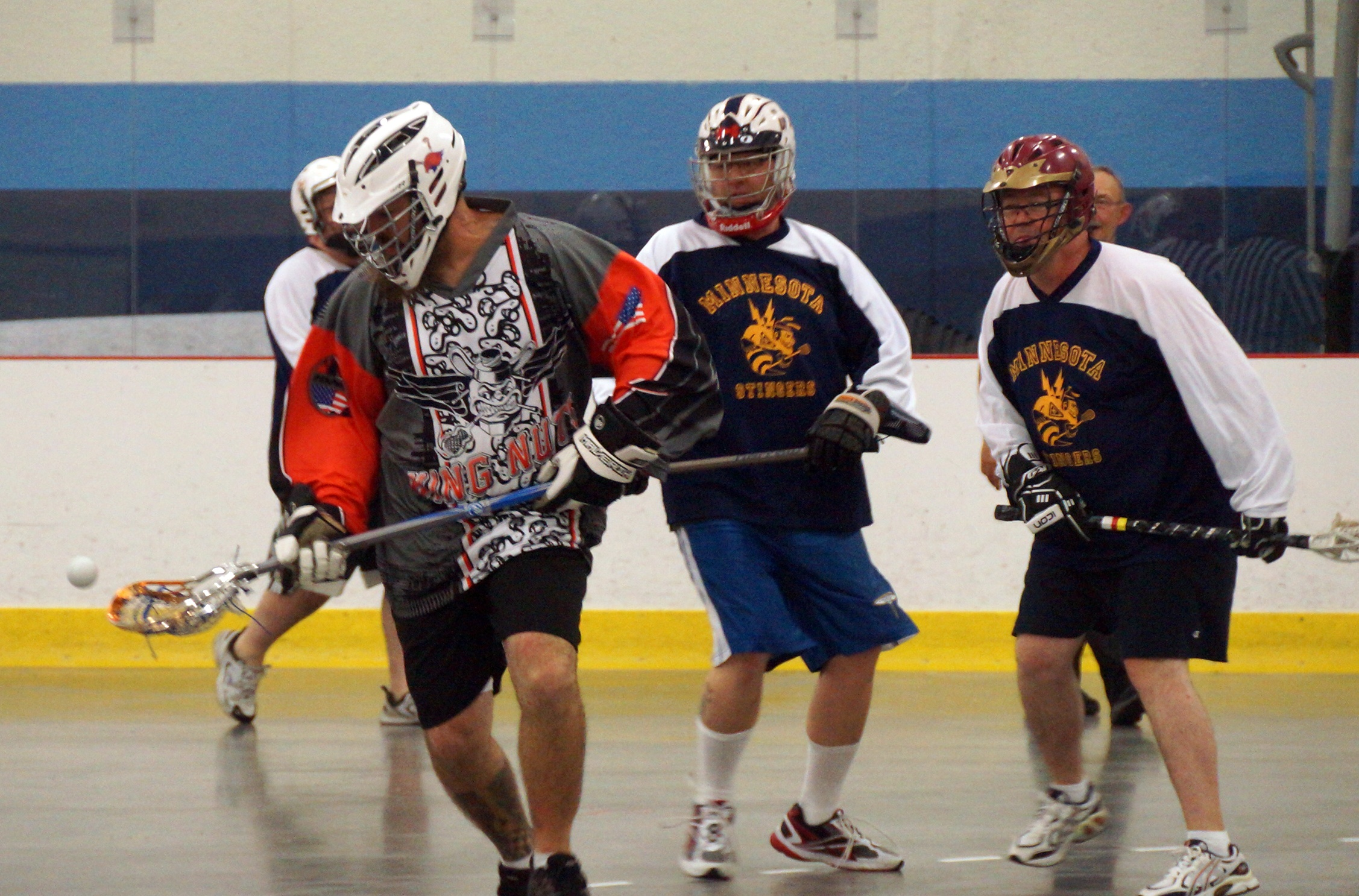 Several men playing box lacrosse in a tournament. Art Coulson is on the right in a maroon helmet and Minnesota Stinghers jersey