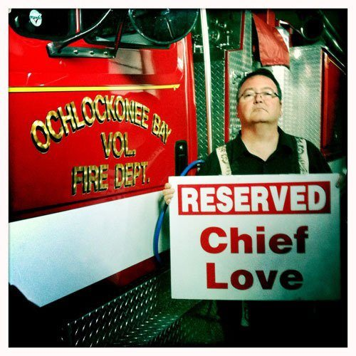 Art Coulson holds a sign that reads Reserved for Chief Love next to a firetruck at the Ochlockonee Bay Volunteer Fire Department in Florida